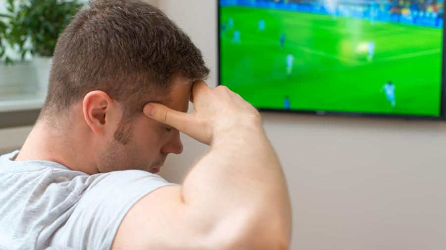 Sad man watching football match on television at home.